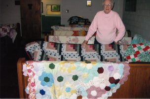 Ruth Morton with her log cabin and other quilts